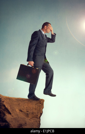 businessman with hands over eyes stepping off the edge of a cliff - Stock Image