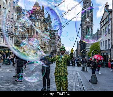 A street performer, Freak Bubbles, on EdinburghÕs Royal Mile creates a sea of bubbles for the passing crowds Credit: Rich Dyson/Alamy Live News - Stock Image