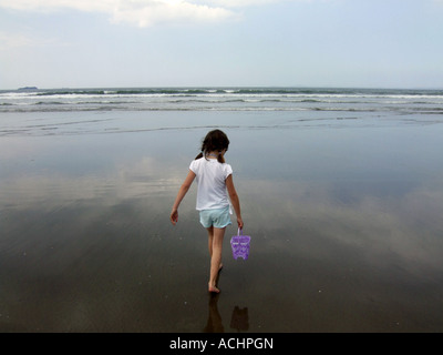 Girl walking out to the sea carrying a bucket, UK - Stock Image