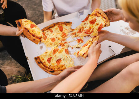 Friends sharing a pizza - Stock Image