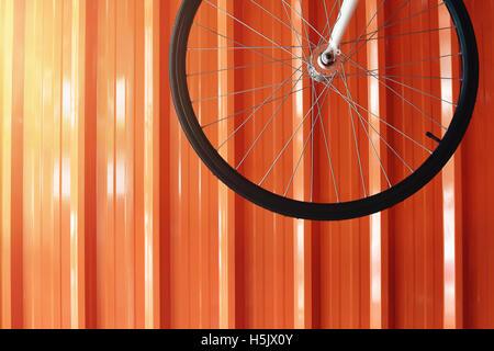 Bicycle Wheel hanging at the Orange Garage Wall - Stock Image