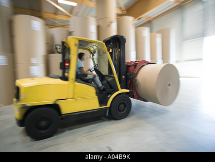 Fork lift carrying roll of paper - Stock Image