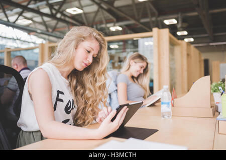 Co-workers working on digital tablet in open plan office - Stock Image