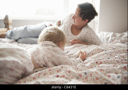 Toddler girl sitting with mother in bed - Stock Image