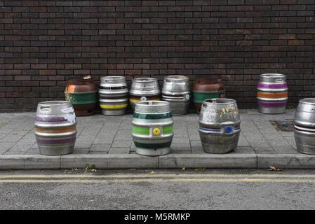 Une sélection de fûts de bière en aluminium avec diverses rayures de couleurs sur le trottoir contre un mur de briques. - Image de l'éditeur