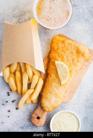 Poisson-frites britannique traditionnel avec sauce tartare et verre de bière artisanale sur une planche à découper, sur fond de pierre blanche. - Image de l'éditeur