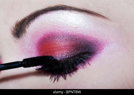 woman applying mascara colored eyeshadow makeup - Stock Image