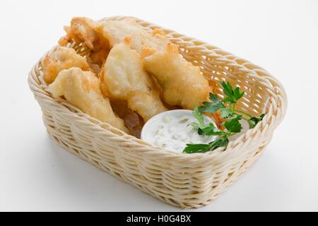 Morue à la pâte à la bière avec une sauce tartare dans un panier de bambou sur fond blanc - Image
