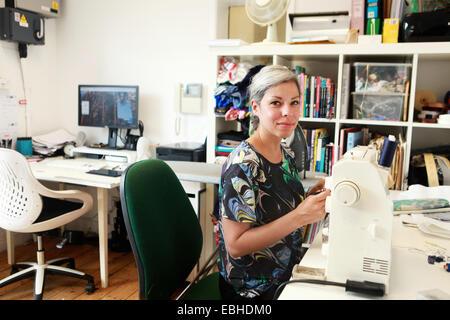 Designer working at sewing machine in studio - Stock Image