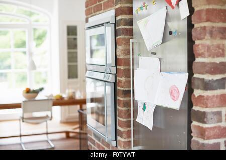 Children's drawings stuck on fridge door - Stock Image
