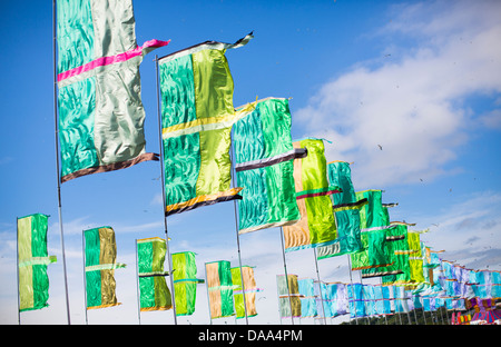 Colourful green and blue flags flutter in the wind at Glastonbury Festival 2013. - Stock Image