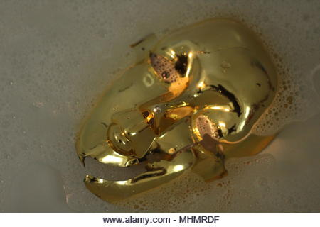 Abstracts & Backgrounds art conceptual - Masque facial en plastique doré flottant dans l'eau. (Performances teintées de thème - pollution des plastiques) - Image