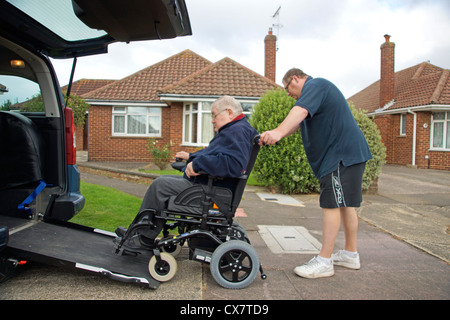 Male Carer son pushing a disabled elderly man in a wheelchair onto a built in ramp in a specially adapted car for - Stock Image