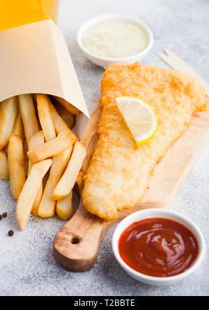 Poisson et frites britanniques traditionnels avec sauce tartare et verre de bière artisanale et de ketchup à la tomate sur une planche à découper sur fond de pierre blanche. - Image de l'éditeur