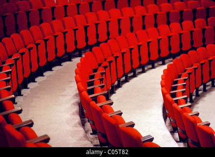 Curved rows of red seats in an auditorium. - Stock Image