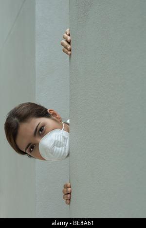 Femme au masque de pollution furtivement au coin - Image