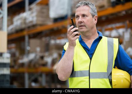 Man on walkie talkie in warehouse - Stock Image