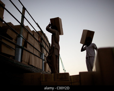 Workers loading traditional dhows after sunset at the dhow wharfage in The Creek, Dubai, UAE - Stock Image