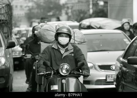 Homme monté sur un scooter portant un masque contre la pollution dans un trafic dense le long de Thanon Yaowarat à Bangkok Chinatown - Image