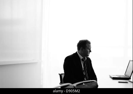 Businessman looking at laptop - Stock Image