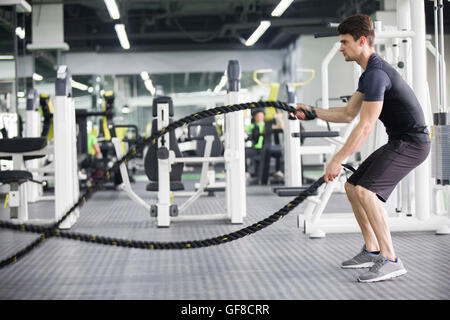 Young man exercising with battling rope at gym - Stock Image