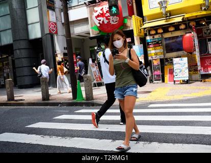 Sur la photo est une fille marchant dans les rues de tokyo Japon - Image