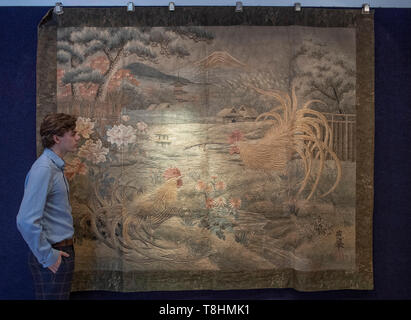 Bonhams, New Bond Street, London, UK. 13th May 2019. A large embroidered wall hanging with two cockerels and Mount Fuji, Meji era, estimate of £2,000-3,000, at Bonhams Fine Japanese Art sale, taking place on 16th May 2019. Credit: Malcolm Park/Alamy Live News. - Stock Image