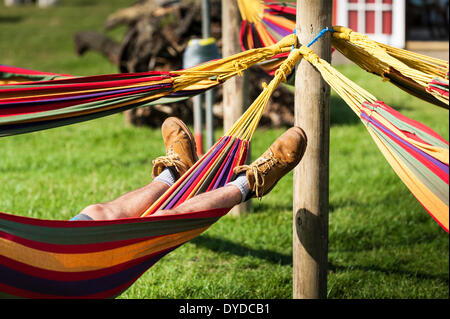 A man sleeping in a hammock at the Brownstock Festival in Essex. - Stock Image