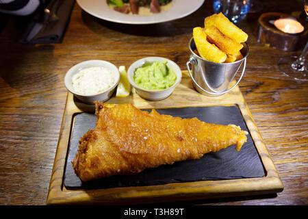 Fish and chips servi avec une sauce tartare et des petits pois. Le poisson pané à la bière a été débarqué à Grimsby. - Image de l'éditeur