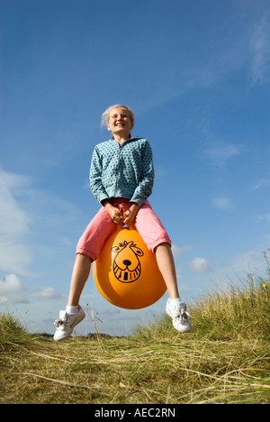 Young girl bouncing on a Space Hopper, England UK - Stock Image