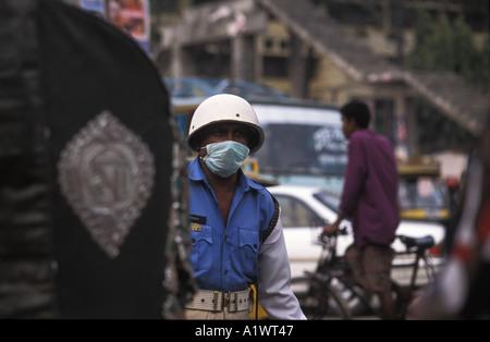 Policier dirigeant le trafic avec un masque pour faire face à la pollution - Image