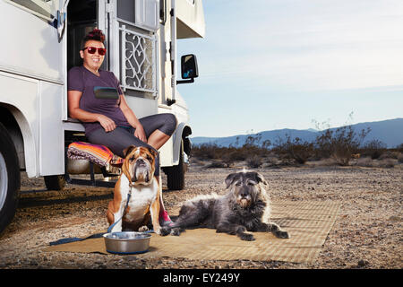 Portrait of mid adult woman and two dogs sitting on camper van step, Borrego Springs, California, USA - Stock Image