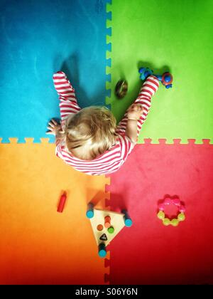 Baby playing on colourful play mat - Stock Image