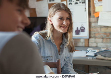 Happy design professional with coworker looking away in workshop - Stock Image