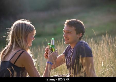 Un jeune couple assis à l'extérieur, buvant de la bière - Image