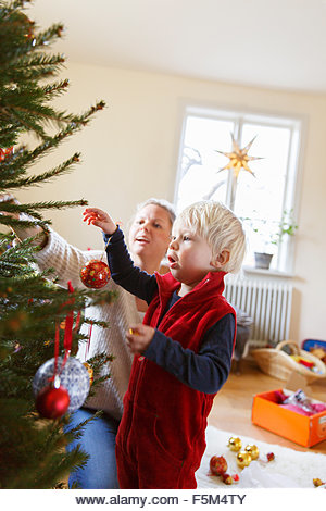 Sweden, Mother with son decorating christmas tree - Stock Image