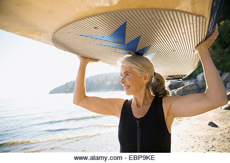 Senior woman holding paddle board overhead on beach - Stock Image