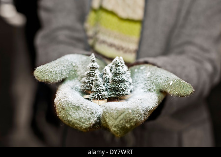 Young woman with gloves holding Christmas decoration, partial view - Stock Image