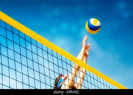 Beachvolley ball player jumps on the net and tries to  blocks the ball - Stock Image