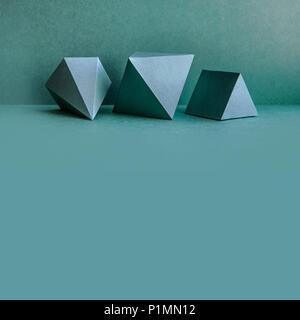 Figures géométriques encore composition de la vie. Objets de cube rectangulaire tétraédrique de pyramide prisme en trois dimensions sur fond vert. Plates-formes de solide platonique, espace copie - Image