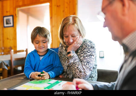Grandparents playing ludo their grandson - Stock Image
