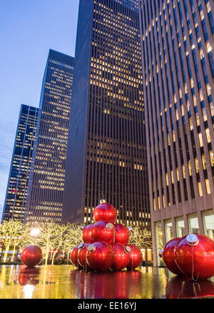 Red Giant Christmas Balls  below the towers. Evening view of huge Christmas balls placed annually in the reflecting - Stock Image