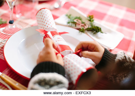 Girl with Christmas cracker at family Christmas party - Stock Image