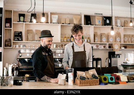 Happy workers working at cafe counter - Stock Image