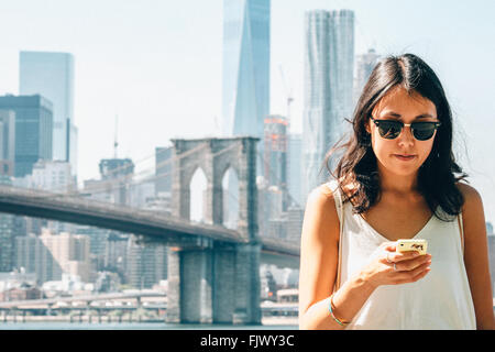 Young Woman Using Smart Phone Against Brooklyn Bridge - Stock Image