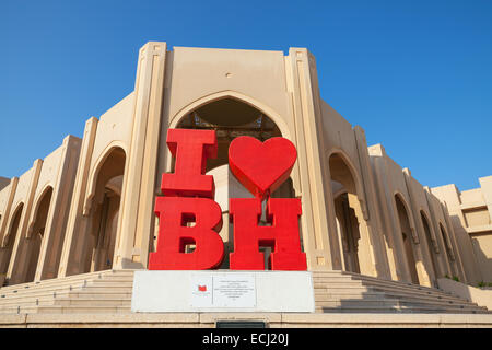Manama, Bahrain - November 21, 2014: Red touristic construction with text I love Bahrain stands on the street of - Stock Image