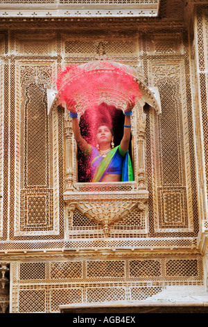 Woman throwing brightly coloured holi powder through a window of a haveli - Stock Image