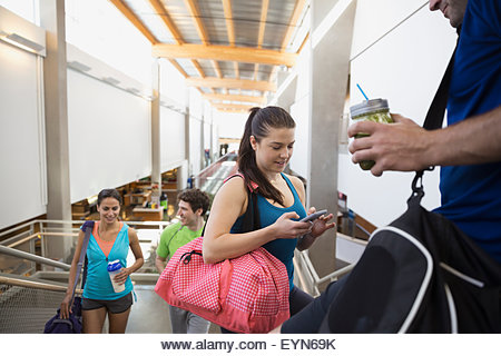 Friends talking and using cell phone at gym - Stock Image