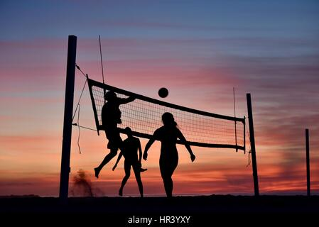 Silhouettes of female volleyball players practicing volleyball on a beach at sunset in Mission Beach, San Diego, - Stock Image