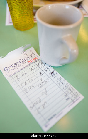 An inside view of an American Diner and the check for the breakfast meal. - Stock Image